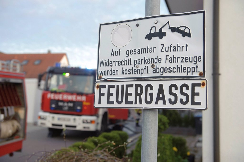Stock Photo: 1848-683528 Sign, Feuergasse freihalten, German for keep clear lane for fire engines, fire engines at back during a fire fighting operation at a barn fire, Aichelberg, Baden_Wuerttemberg, Germany, Europe