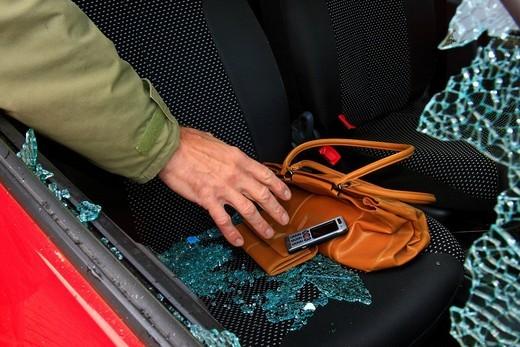 Car burglary, hand grasps through the side window at valuables, i.e. handbag, purse and mobile phone : Stock Photo