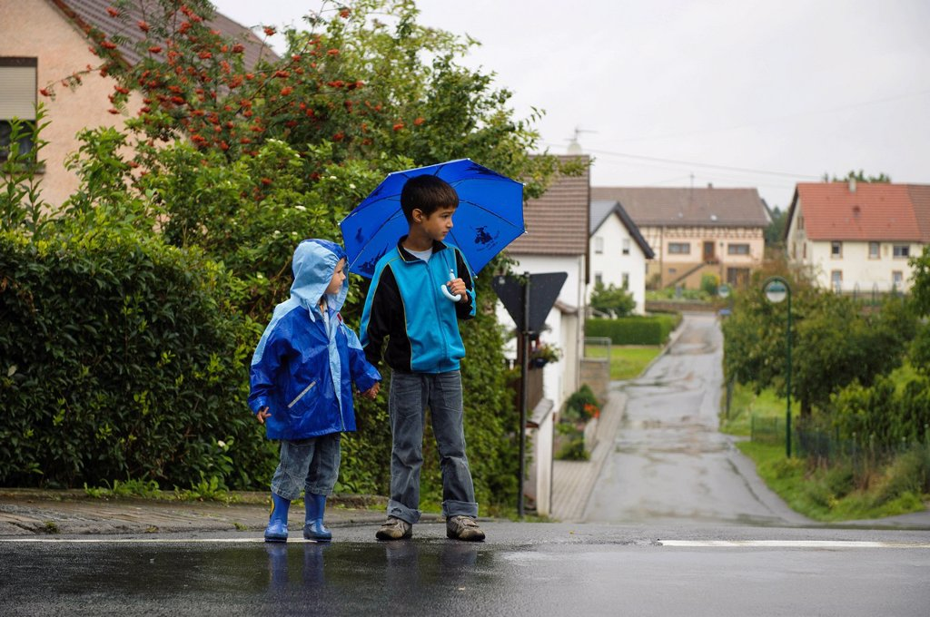 Stock Photo: 1848-687117 Two children, 4 and 8 years, crossing the street in the rain, Assamstadt, Baden_Wuerttemberg, Germany, Europe