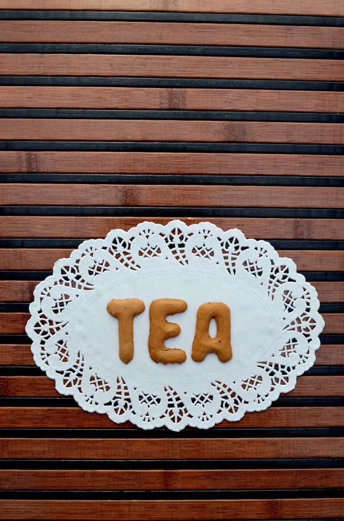 Tea, written with alphabet biscuits on a paper doily : Stock Photo