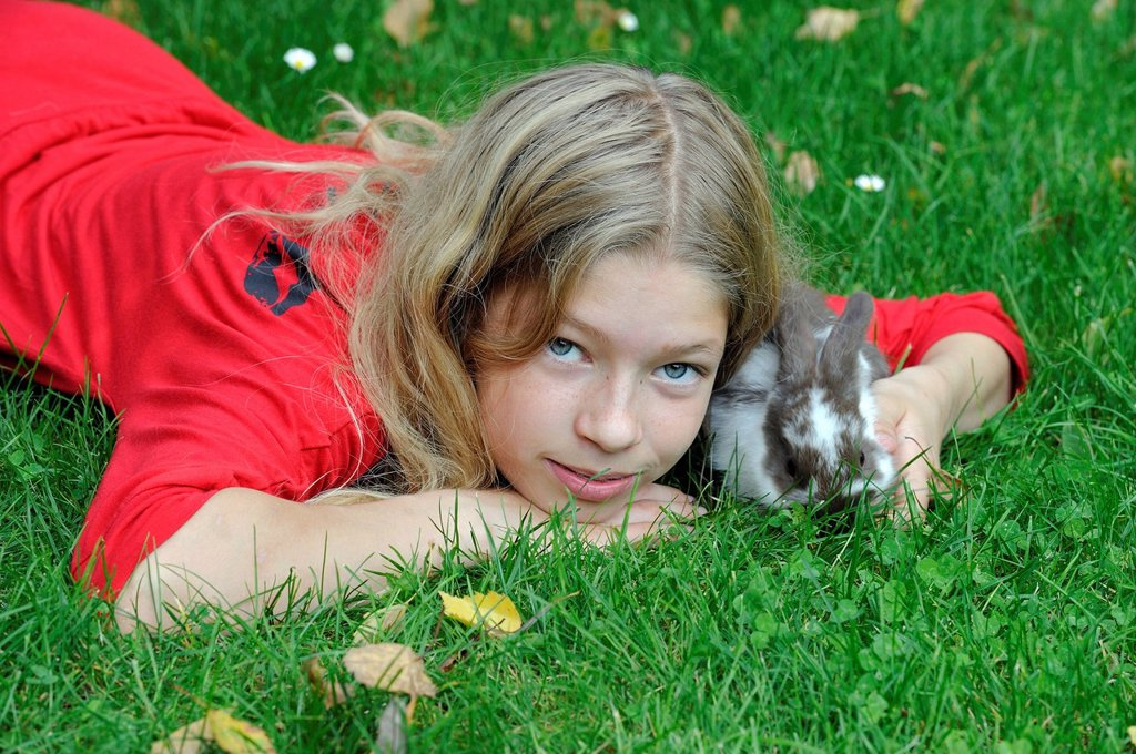 Stock Photo: 1848-690373 Girl, 11, cuddling with a young Domestic Rabbit Oryctolagus cuniculus forma domestica on a meadow
