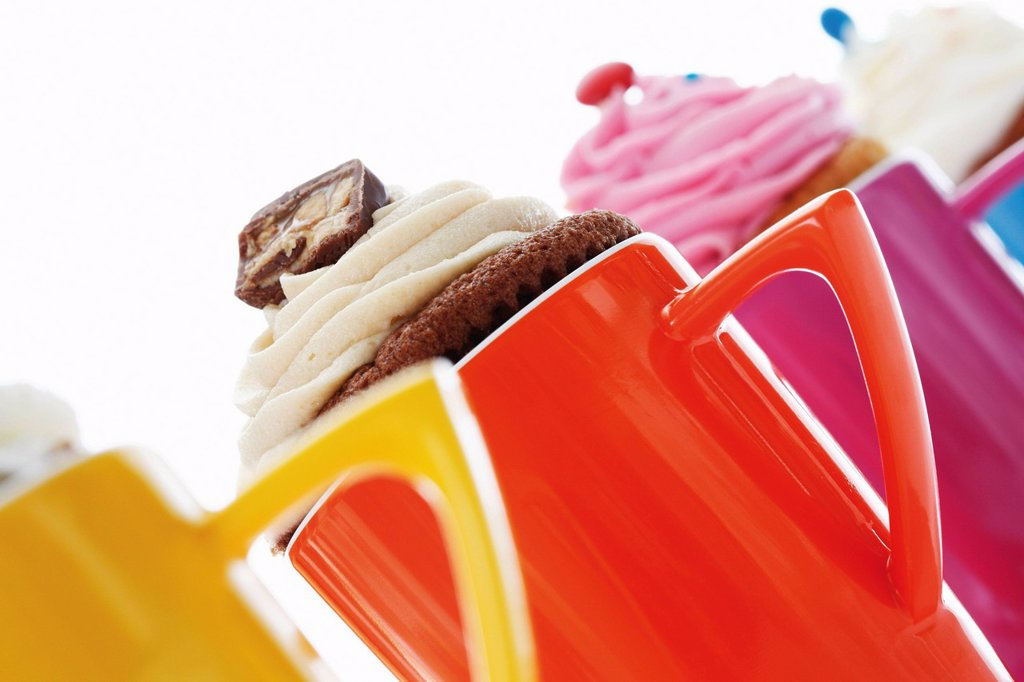 Various cupcakes in colourful coffee mugs : Stock Photo