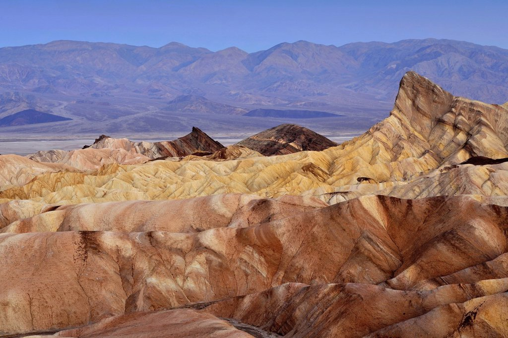 Stock Photo: 1848-692136 View from Zabriskie Point towards Manly Beacon with eroded rocks discoloured by minerals, with Panamint Range in the distance, dawn, Death Valley National Park, Mojave Desert, California, United States of America, USA