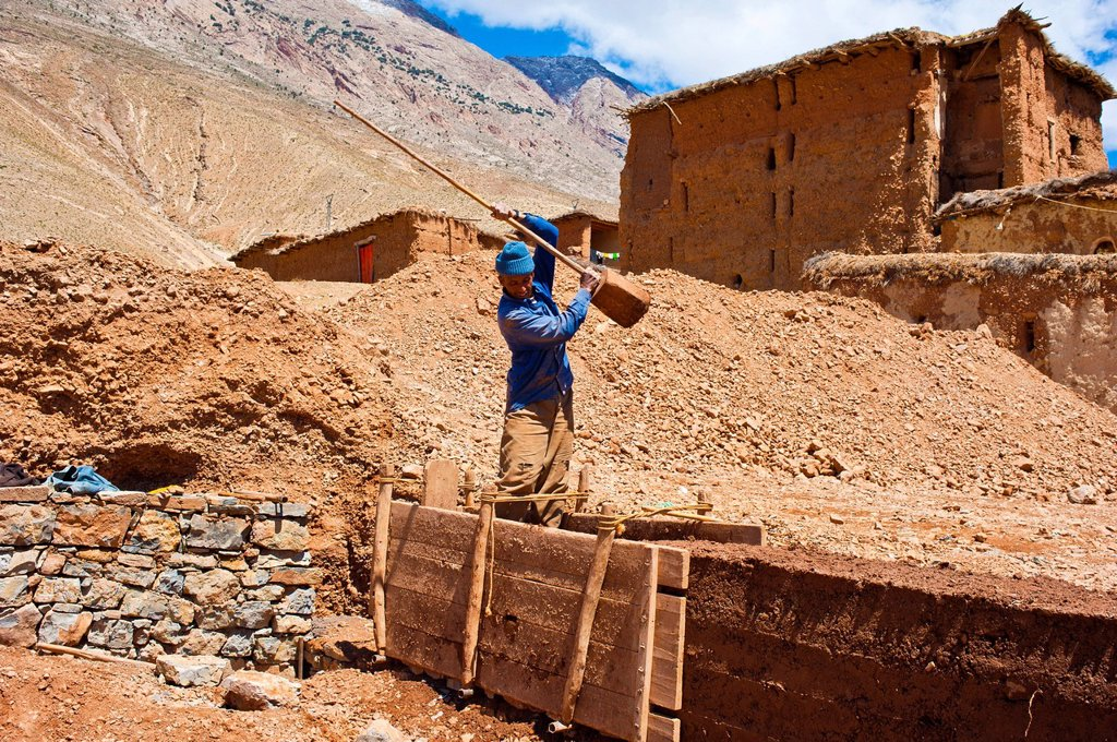 Worker building a rammed_earth wall for a new house, the clay is compacted in a mould box with a wooden pestle, Ait Bouguemez, High Atlas Mountains, Morocco, Africa : Stock Photo