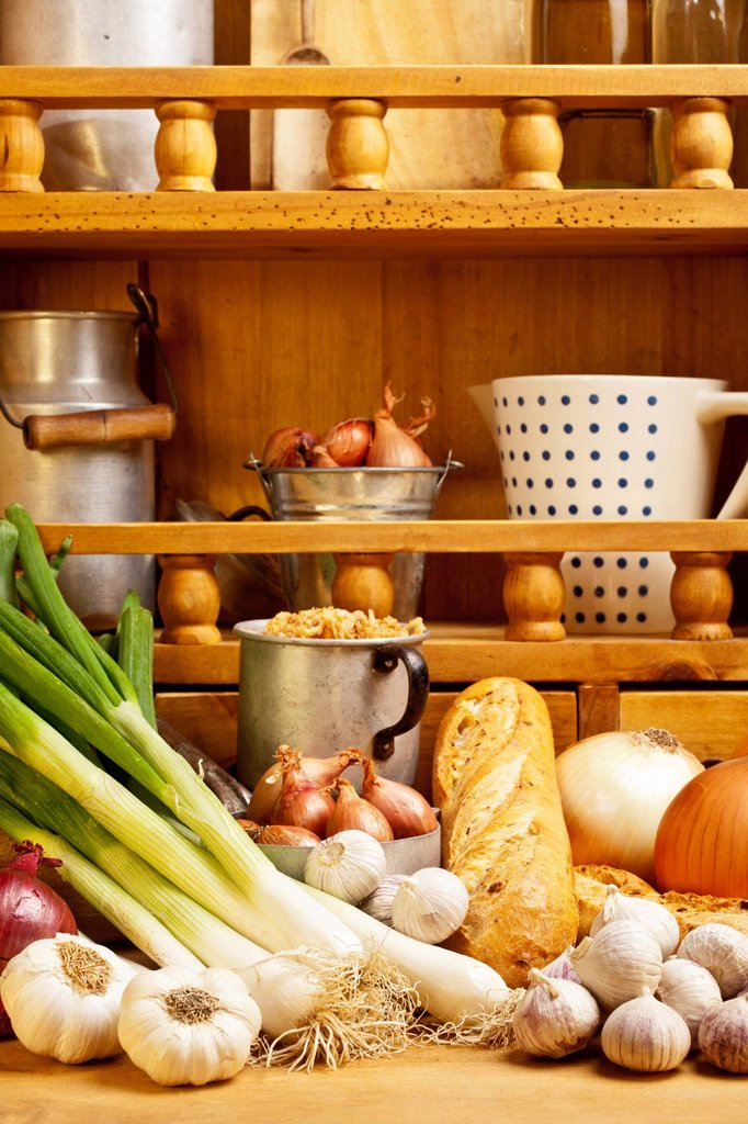 Stock Photo: 1848-694073 Different types of onions and garlic, and onion bread lying on a table, a shelf with spices at the back