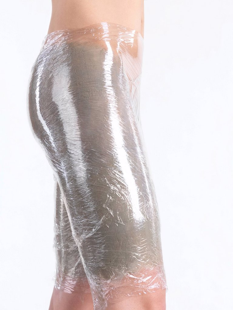Stock Photo: 1848-694210 Woman with bentonite clay mask and plastic body wrap on her thighs and buttocks