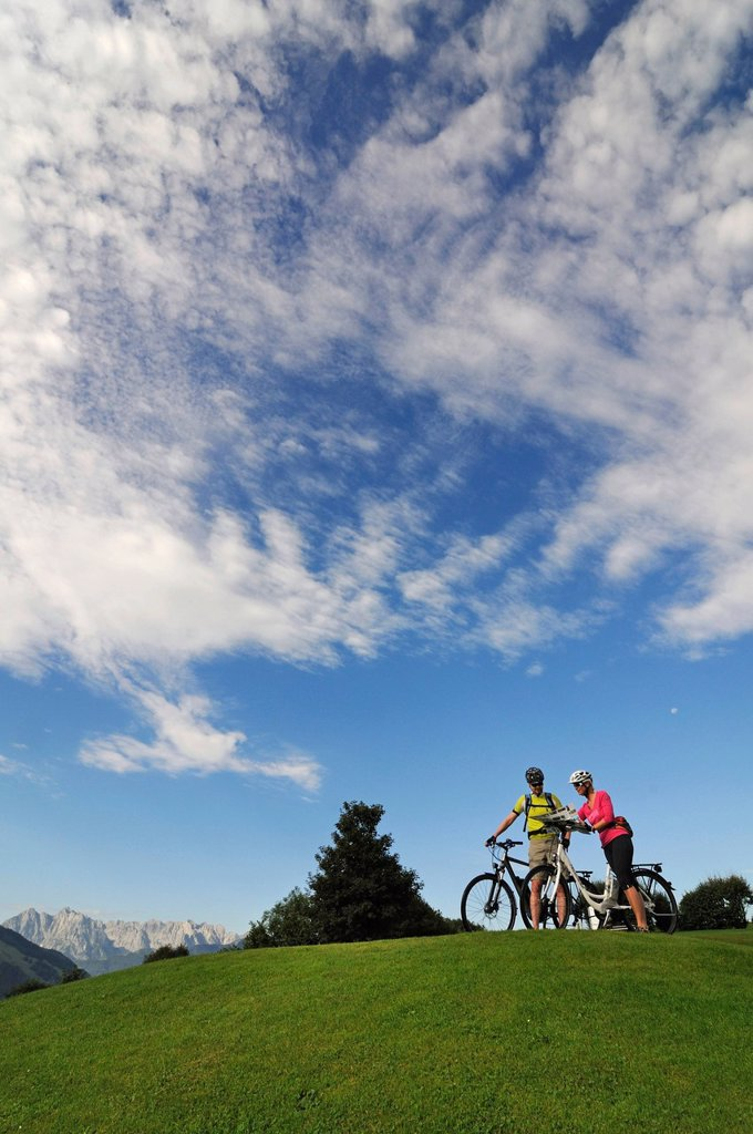 Stock Photo: 1848-694628 A couple riding electric bicycles, Wilder Kaiser mountain at the back, Reit im Winkl, Chiemgau, Upper Bavaria, Bavaria, Germany, Europe