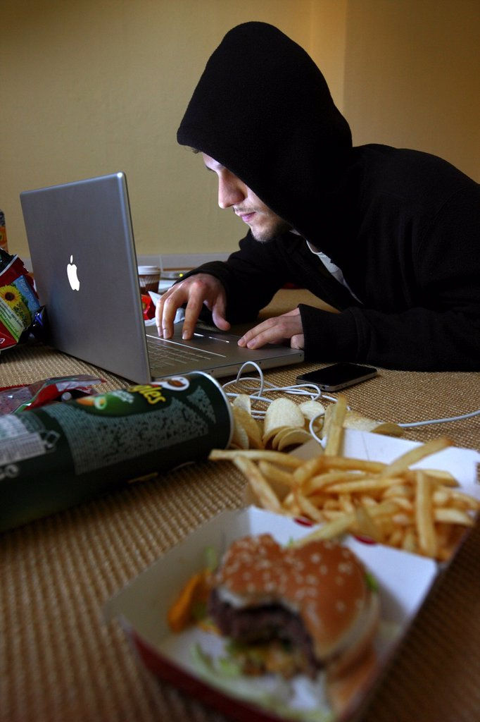 Stock Photo: 1848-696341 Hacker working on a laptop computer in a sparsely furnished apartment, symbolic image for computer hacking, computer crime, cybercrime, data theft