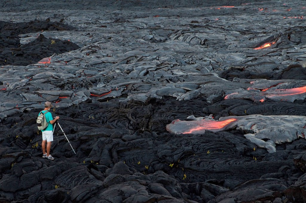 Stock Photo: 1848-697241 Photographer taking pictures of low viscosity lava, P&257,hoehoe lava, flowing from rifts in the East Rift Zone towards the sea, lava field at the Kilauea shield volcano, Volcanoes National Park, Kalapana, Hawaii, USA