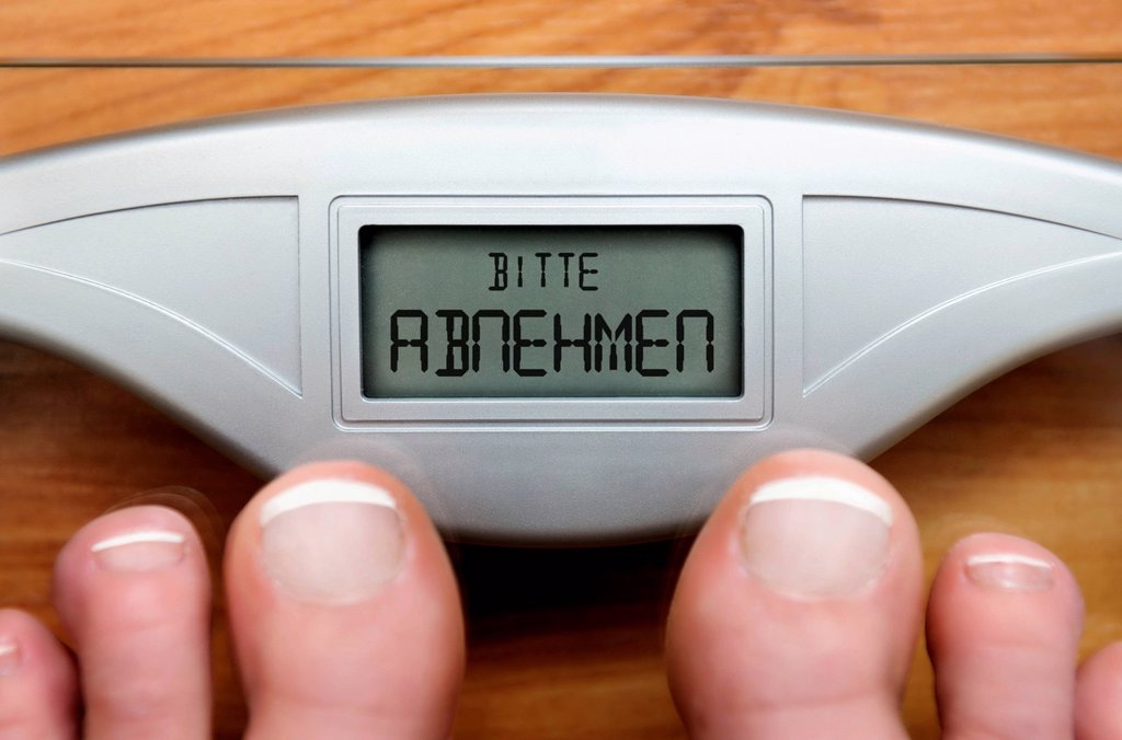 Feet on scales with a digital display and the lettering ´´Bitte abnehmen´´, German for ´´please lose weight´´ : Stock Photo