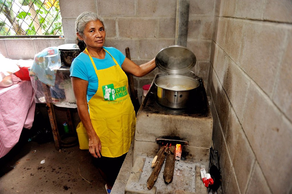 Female cook lifting the lid of a pot, cooking on an energy_saving stove, community of Cerro Verde, El Salvador, Central America, Latin America : Stock Photo