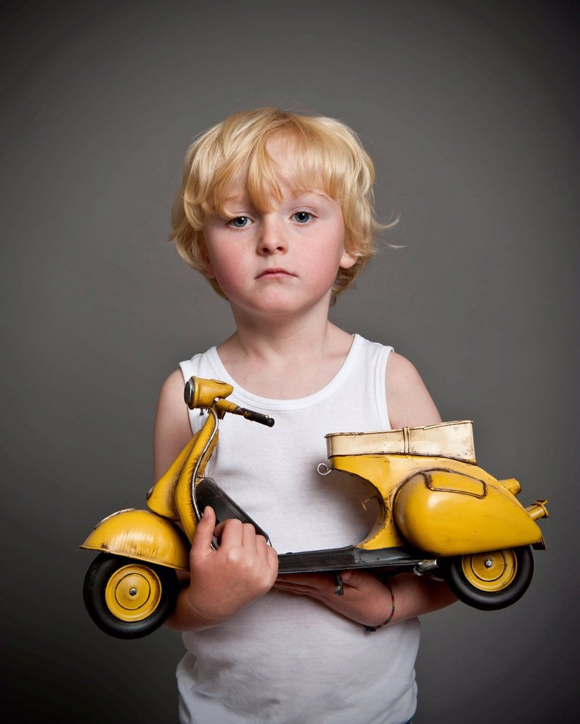 Five_year_old boy holding a toy Vespa scooter, gift, sad face : Stock Photo