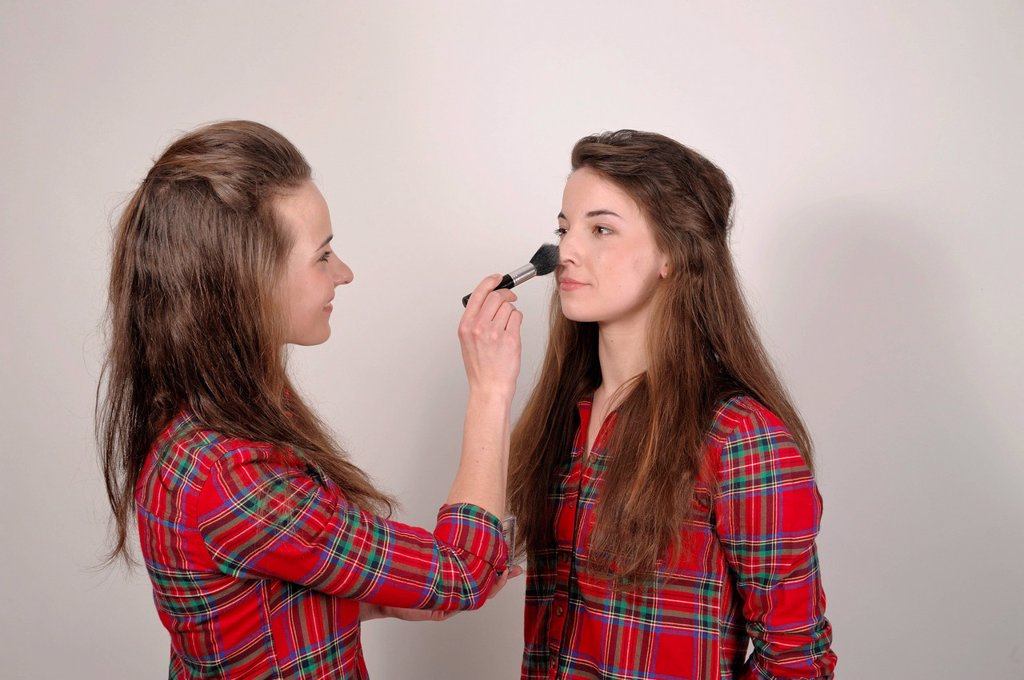 Stock Photo: 1848-700398 Twin sisters, one applying make_up to the other with a brush and powder