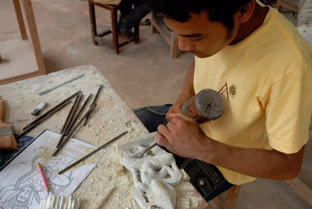 Young Cambodian artisan during the artistic craftsmanship of stone with a wooden hammer and a chisel to produce a traditional Apsara figure, Apsara dancer, Artisans d´Angkor, Angkor, Siem Reap, Cambodia, Indochina, Southeast Asia, Asia : Stock Photo