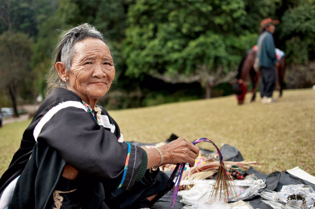 Stock Photo: 1848-701575 Senior hill tribe woman selling souvenirs at a royal project in north Thailand, Asia