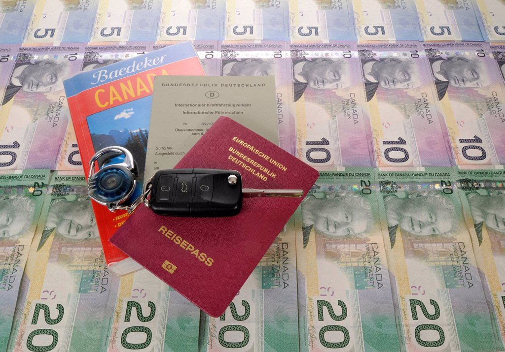 Stock Photo: 1848-704253 Ignition key, international driving license, passport of the Federal Republic of Germany, guide book for Canada and various Canadian dollar banknotes