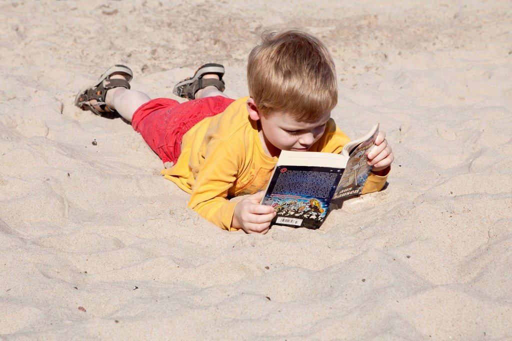 Young boy reading on a beach, Kuehlungsborn_West, Mecklenburg_Western Pomerania, Germany, Europe : Stock Photo