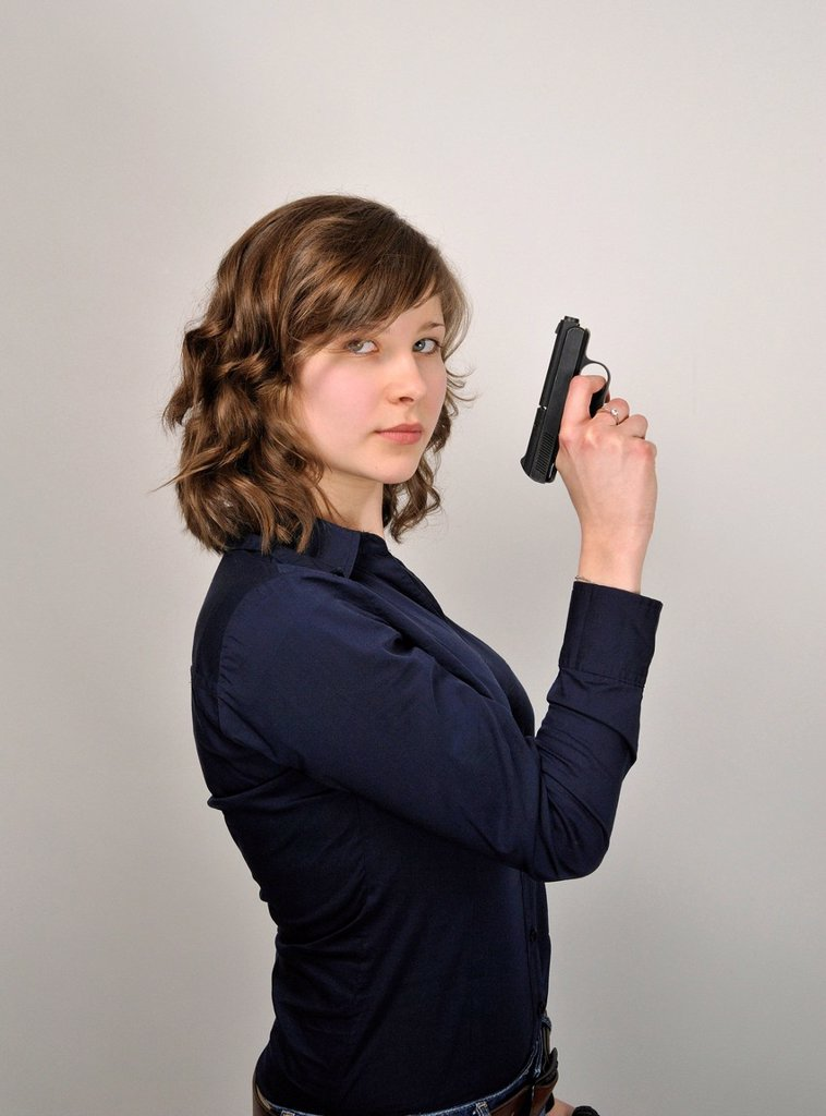 Stock Photo: 1848-706763 Young woman, 20, holding a pistol