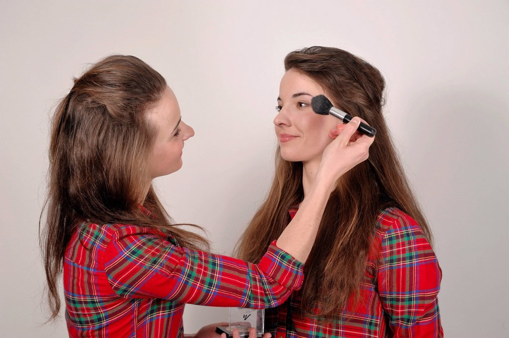 Stock Photo: 1848-708116 Twin sisters, one applying make_up to the other with a brush and powder