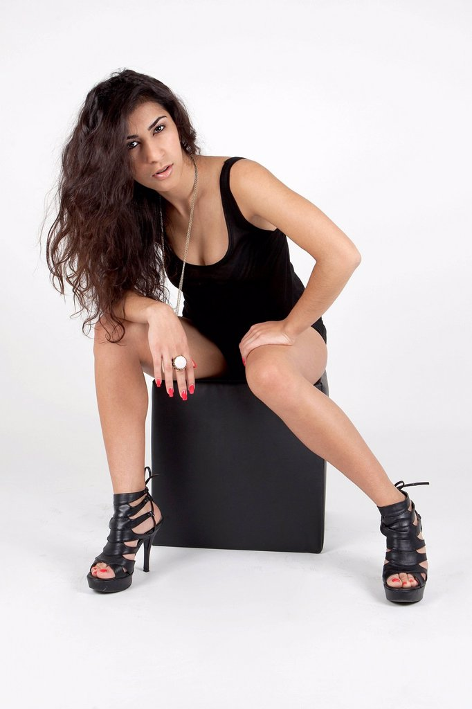 Stock Photo: 1848-708365 Young woman wearing a black top, hot pants and high heels posing with a black cube seat