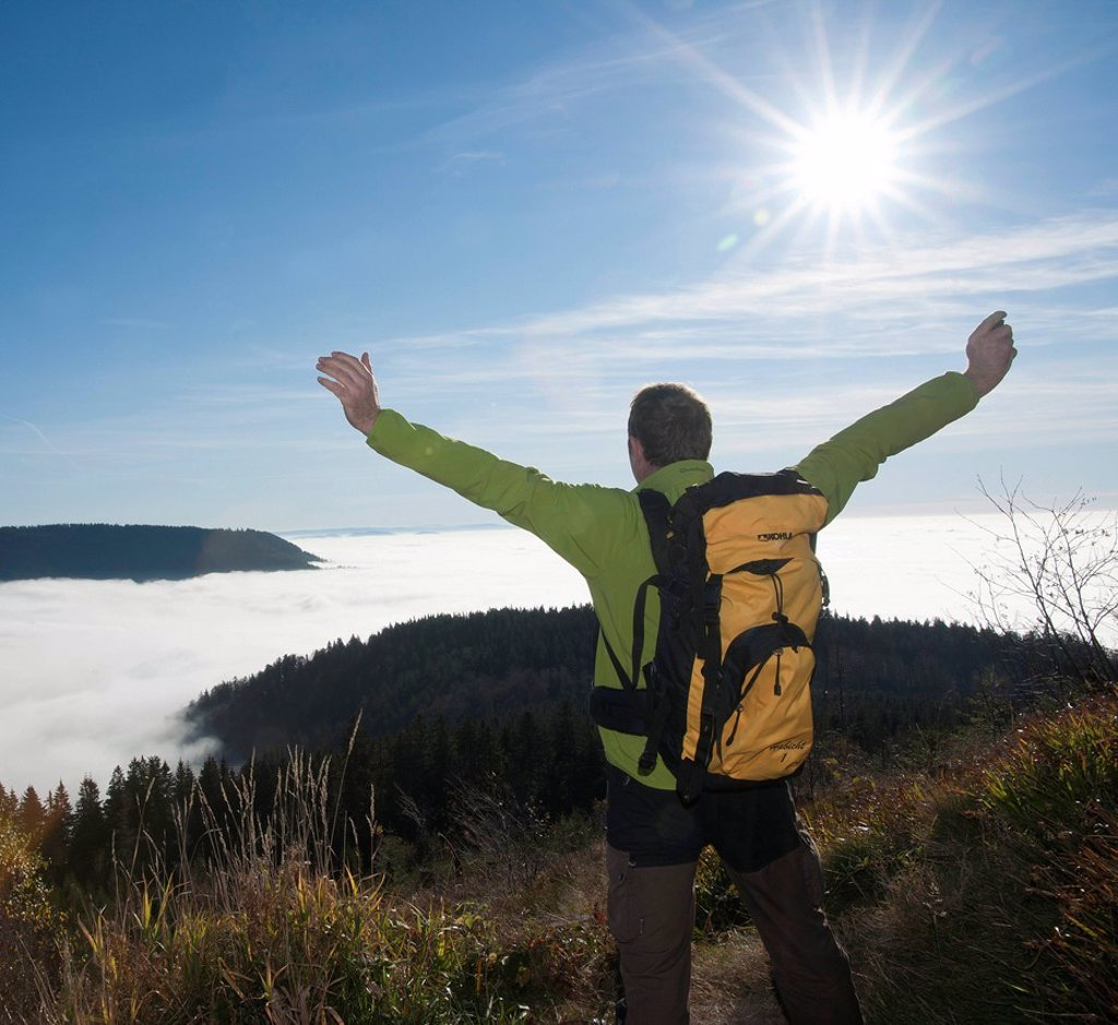 Stock Photo: 1848-710029 Hiker with outstretched arms looking at a fog shrouded valley, Black Forest, Baden_Wuerttemberg, Germany, Europe