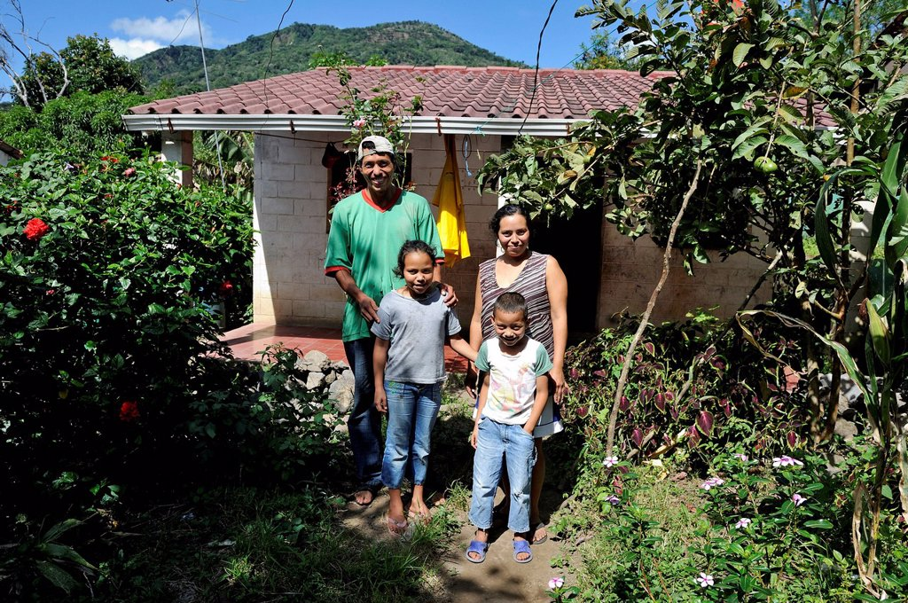 Family with two children in front of their house that was made available to them by an aid organisation after the 2011 earthquake, community of Cerro Verde, El Salvador, Central America, Latin America : Stock Photo