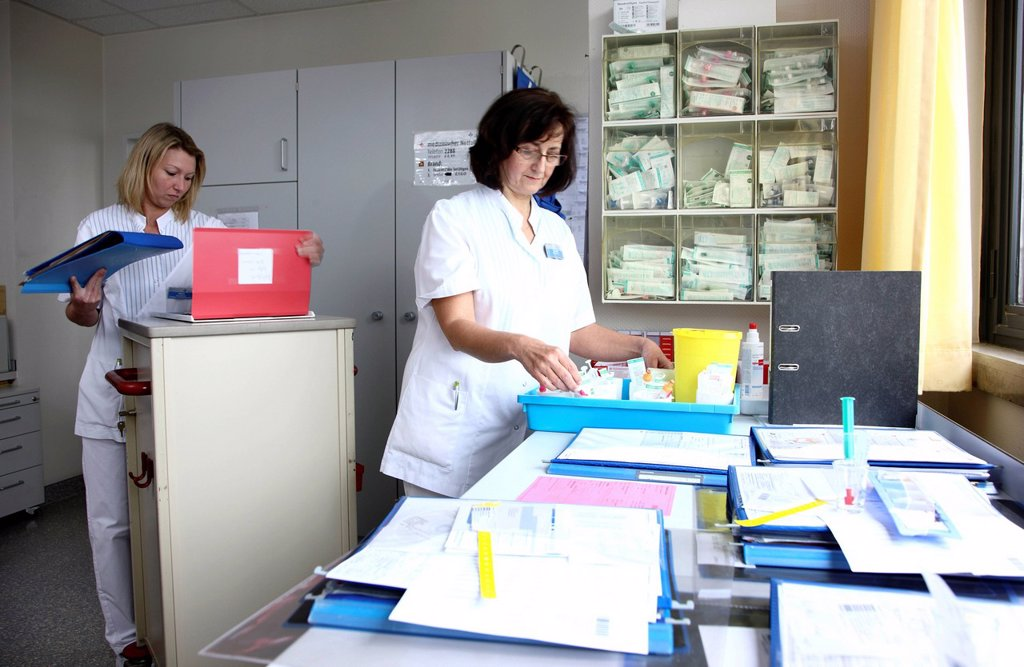 Nurses preparing the documents and medicine for patients in the nurse´s station of a hospital : Stock Photo