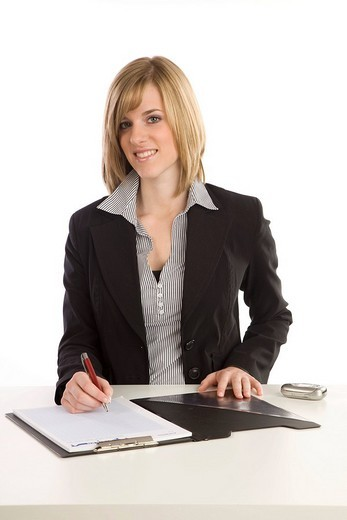 Young blonde woman at a desk writing a note : Stock Photo