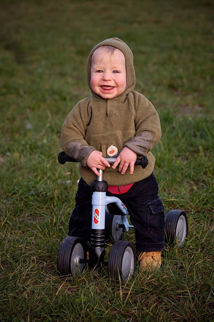 Young boy, 1, seated on a four_wheel Puky push bike, learning to walk, looking happy, Germany : Stock Photo