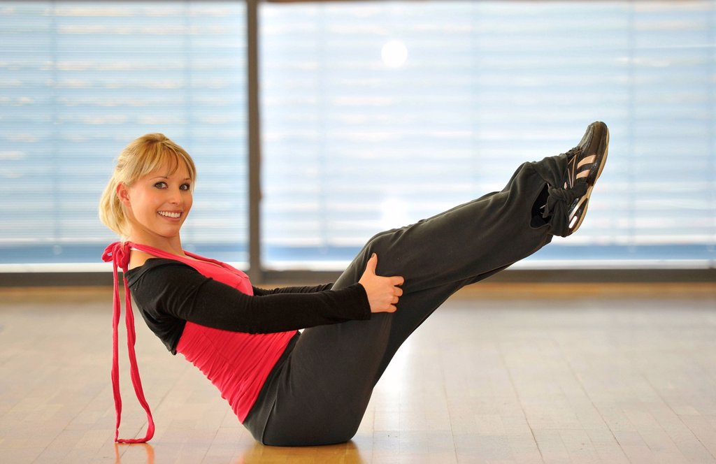 Young woman stretching, warming_up exercises, balancing exercise, yoga, Haus des Sports, House of Sport, SpOrt, Stuttgart, Baden_Wuerttemberg, Germany, Europe : Stock Photo