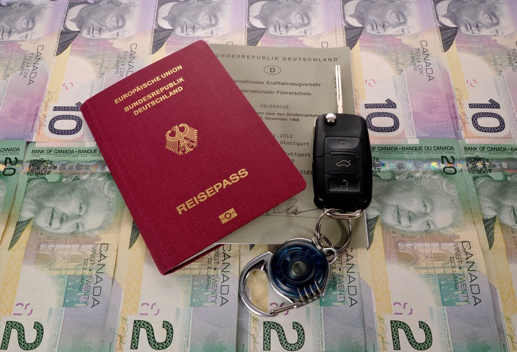 Passport of the Federal Republic of Germany, international driving license, an ignition key and various Canadian dollar banknotes : Stock Photo