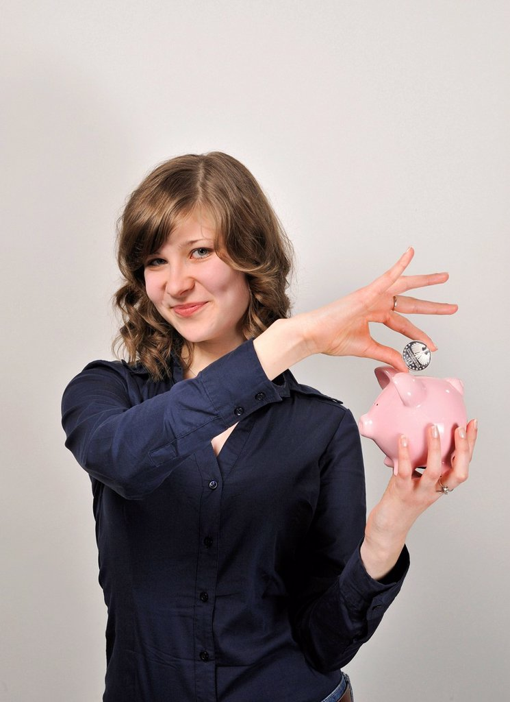 Young woman, 20, putting a 10 euro silver coin in a pink piggy bank : Stock Photo