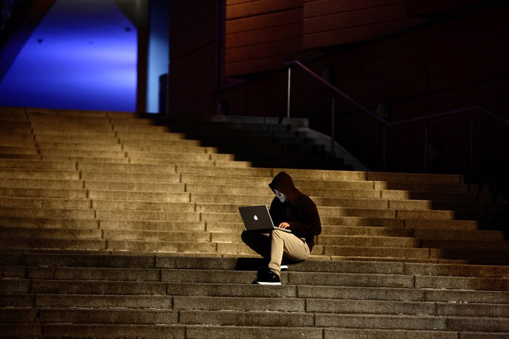 Man surfing on a laptop computer on a staircase at dusk, symbolic image for computer hacking, computer crime, cybercrime, data theft : Stock Photo