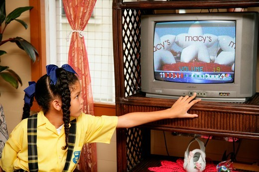 Stock Photo: 1848-72067 Girl wearing school uniform watching TV, Georgetown, Guyana, South America