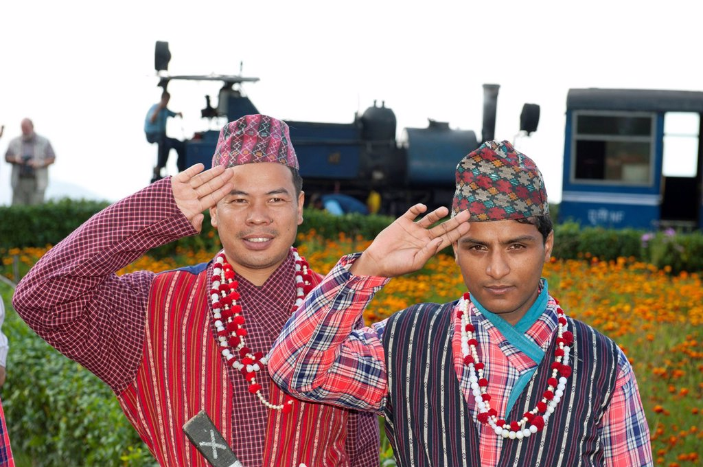 Two Nepali men in traditional costume saluting, historic train at back, Darjeeling Himalayan Railway, narrow_gauge railway, Toy Train, UNESCO World Heritage Site, Darjeeling, West Bengal, India, South Asia, Asia : Stock Photo