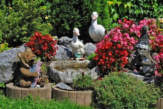 Garden gnomes and figurines of ducks, squirrels and a bear in a Bavarian garden near Munich, Germany, Europe : Stock Photo