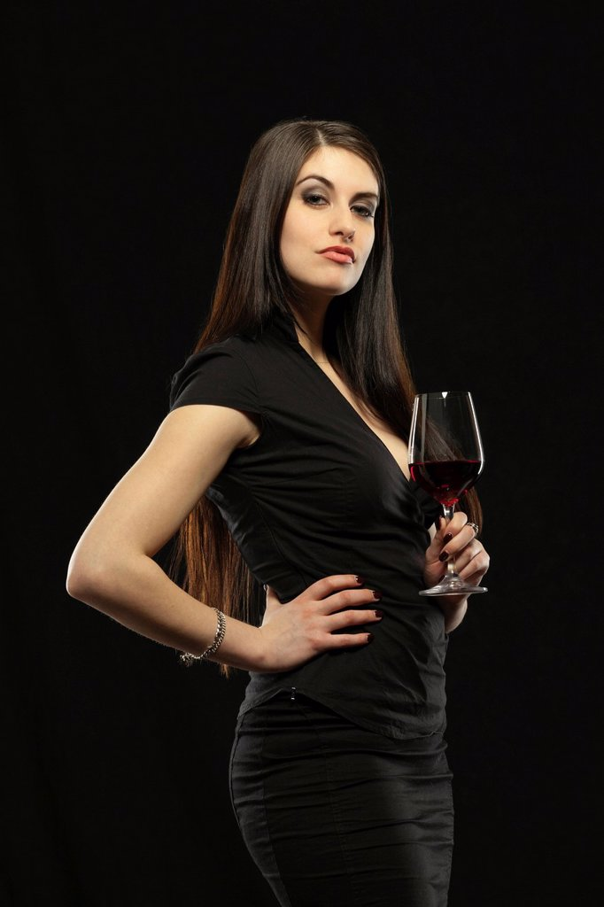 Stock Photo: 1848-724821 Young woman in evening dress holding a glass of red wine