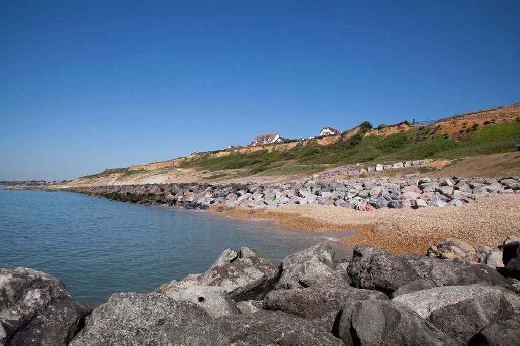 Cliff top houses and rock stone groynes sea defences at Barton on Sea, Hampshire, England, United Kingdom, Europe : Stock Photo
