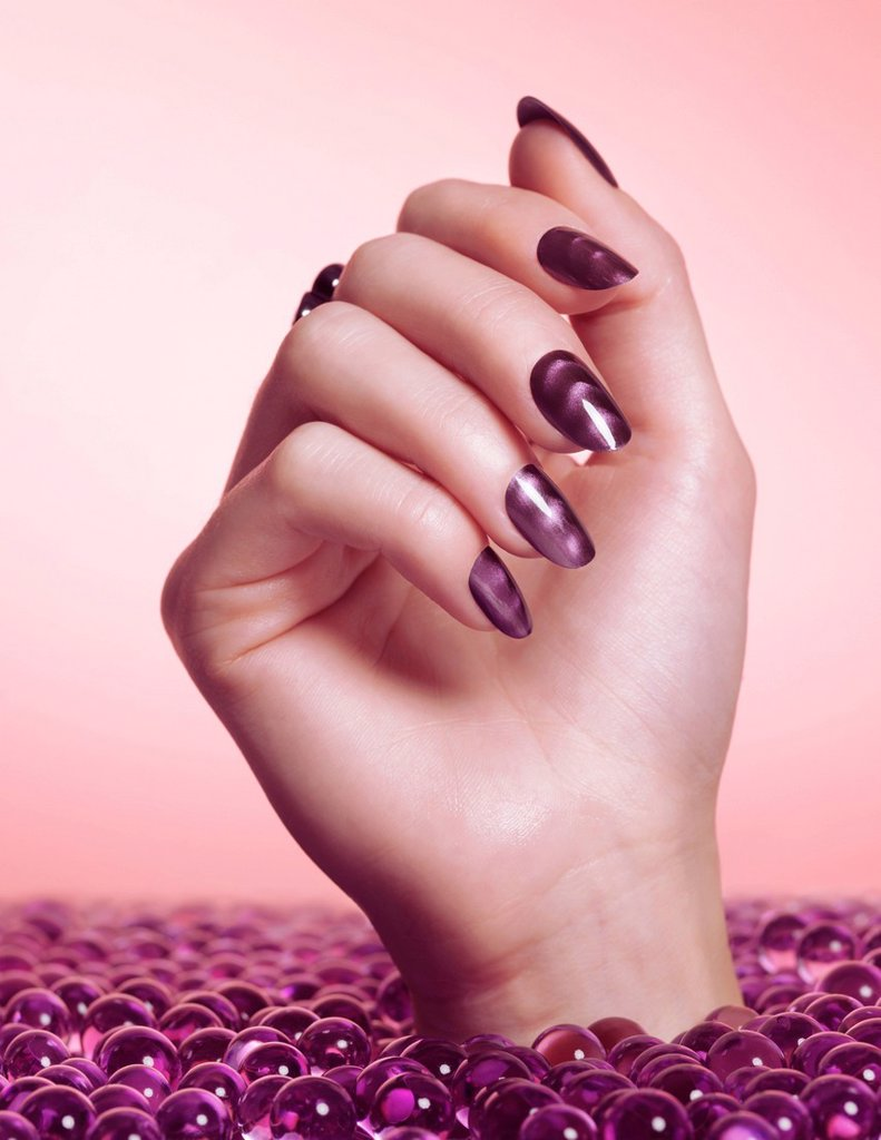 Stock Photo: 1848-725693 Woman´s hand with purple nail polish coming out of purple beads