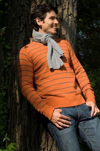 Man wearing a scarf leaning against a tree : Stock Photo