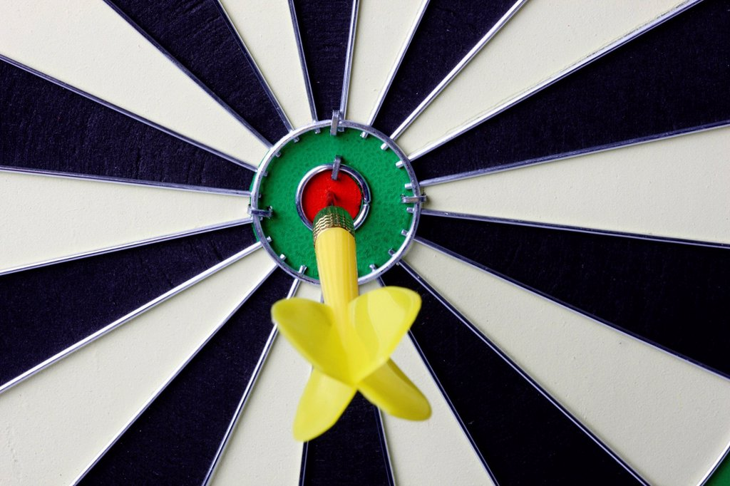 Darts, throwing game, dart sticking into the middle of the dartboard, the bullseye : Stock Photo