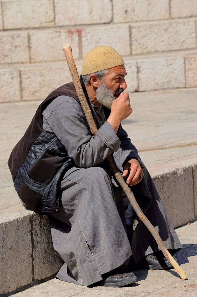 Stock Photo: 1848-726422 Palestinian man sitting on the steps outside the Damascus Gate in front of the Old City, Jerusalem, Israel, Middle East, Southwest Asia