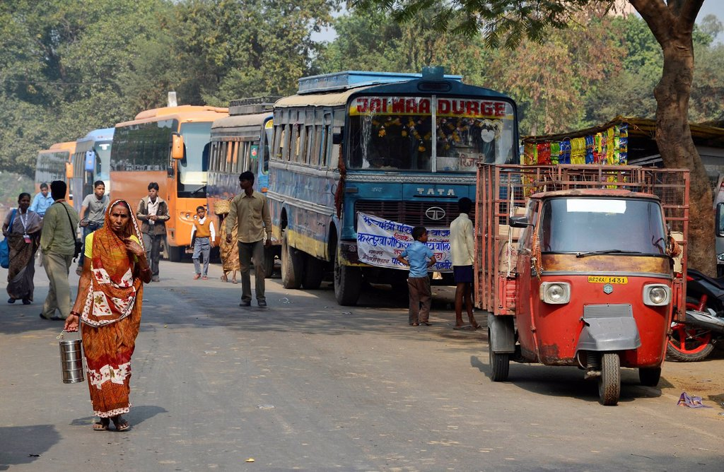 Street scene with Indian pilgrim buses, tuk tuk and pedestrians outside the ruins of the ancient University of Nalanda, Ragir, Bihar, India, Asia : Stock Photo