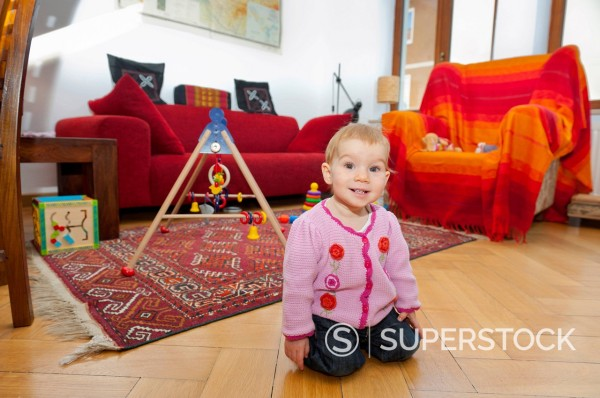 Stock Photo: 1848-728510 Smiling toddler, girl playing on the floor in the living room, Munich, Bavaria, Germany, Europe