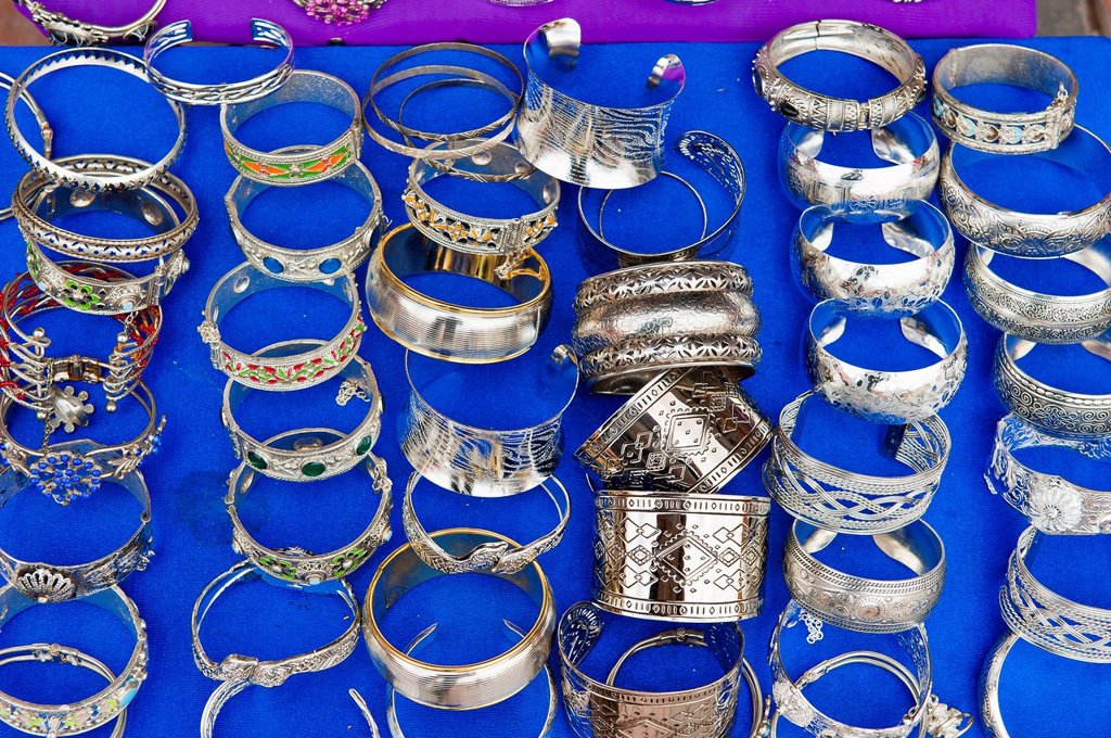 Ornately decorated silver bangles on a blue cloth for sale, souks, bazaar area, Marrakech, Morocco, Africa : Stock Photo