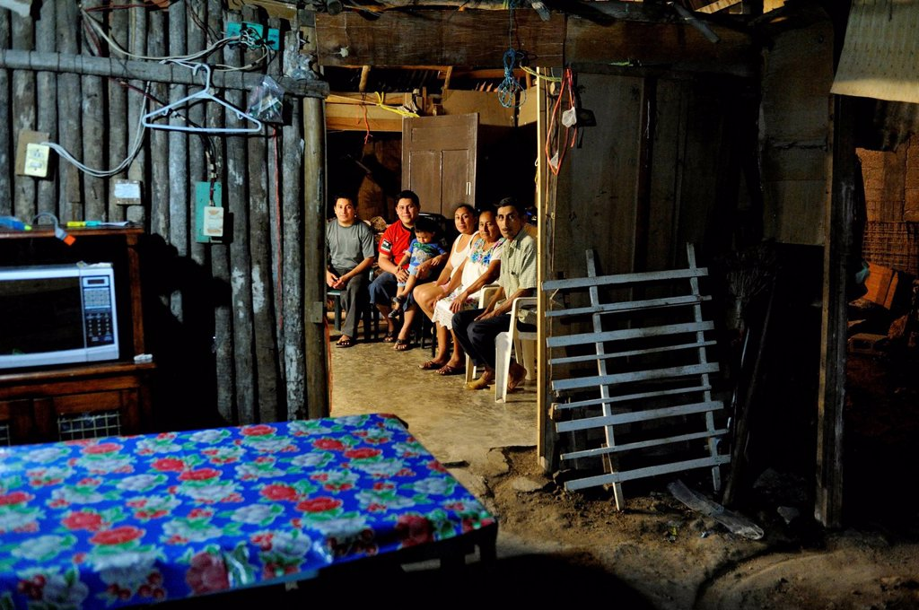 Family of a couple that works in the tourism industry, people sitting in a humble wooden hut at night, on the outskirts of Cancun, Yucatan Peninsula, Quintana Roo, Mexico, Latin America, North America : Stock Photo