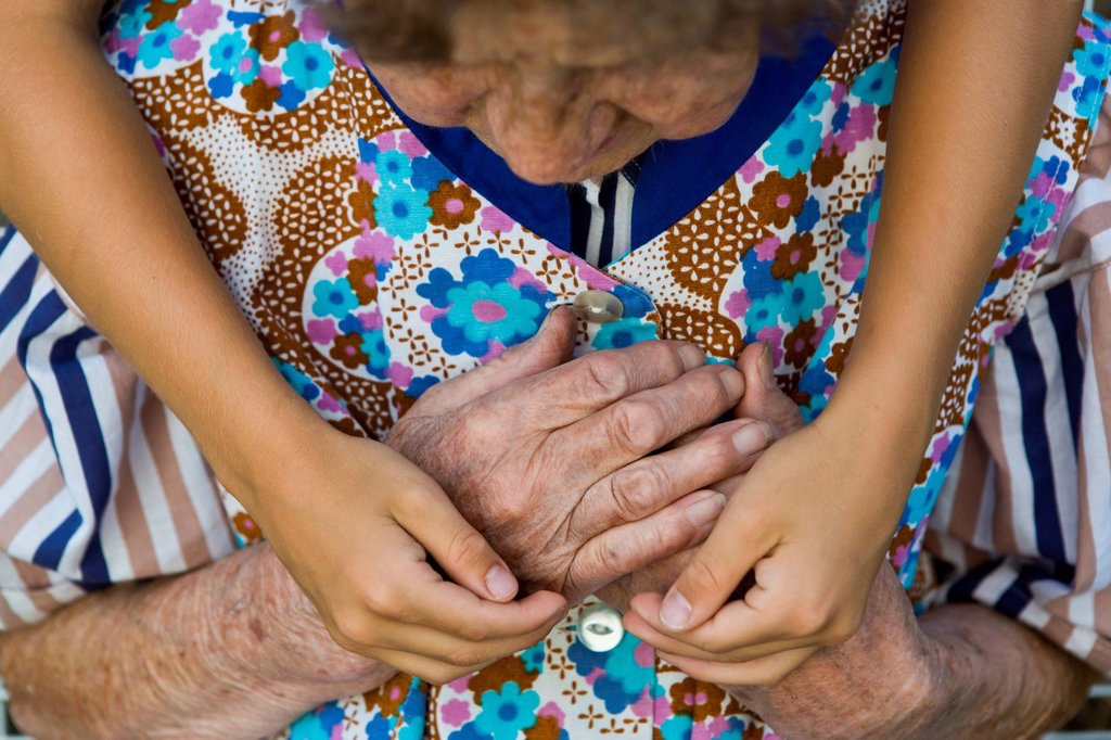 Child hugging an elderly woman : Stock Photo