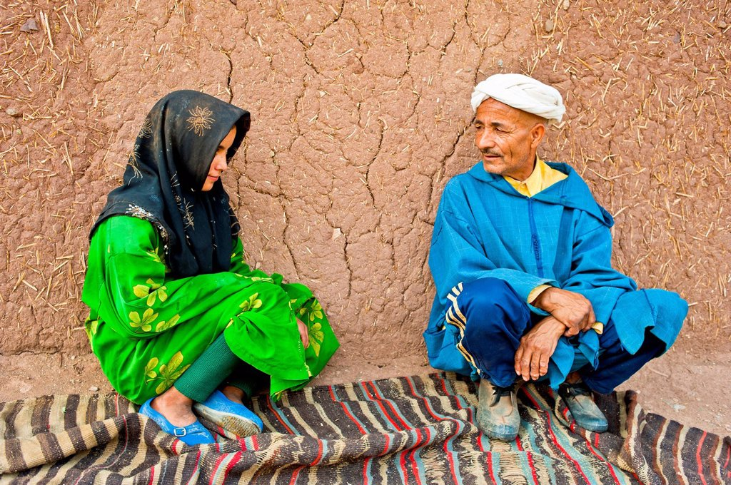 Stock Photo: 1848-732931 Elderly man and a young girl, Berber people, squatting on a carpet or rug in front of a mud brick house talking, High Atlas mountain range, Morocco, Africa