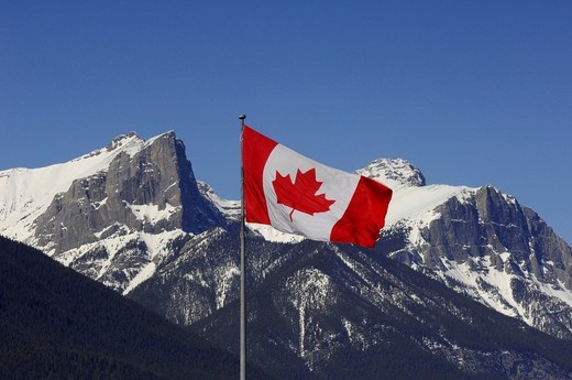 Canadian flag against a backdrop of the Canadian Rocky Mountains, Canmore, Alberta, Canada : Stock Photo