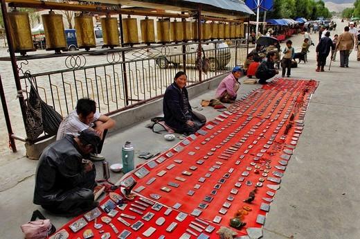 Souvenir dealers, sitting in front of prayer mills, entrance of Palcho Monastery or Pelkor Chode Monastery or Shekar Gyantse, Gyantse, Tibet : Stock Photo